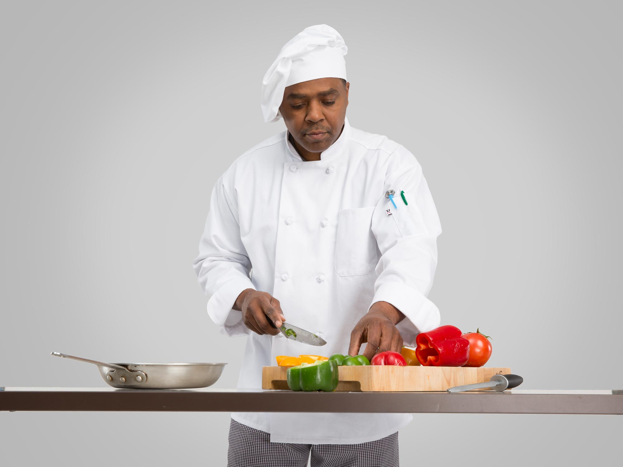 Male chef slicing vegetables