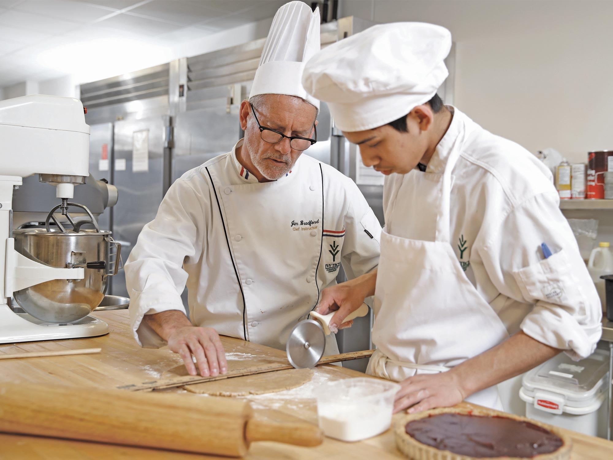 Male student and instructor working in kitchen