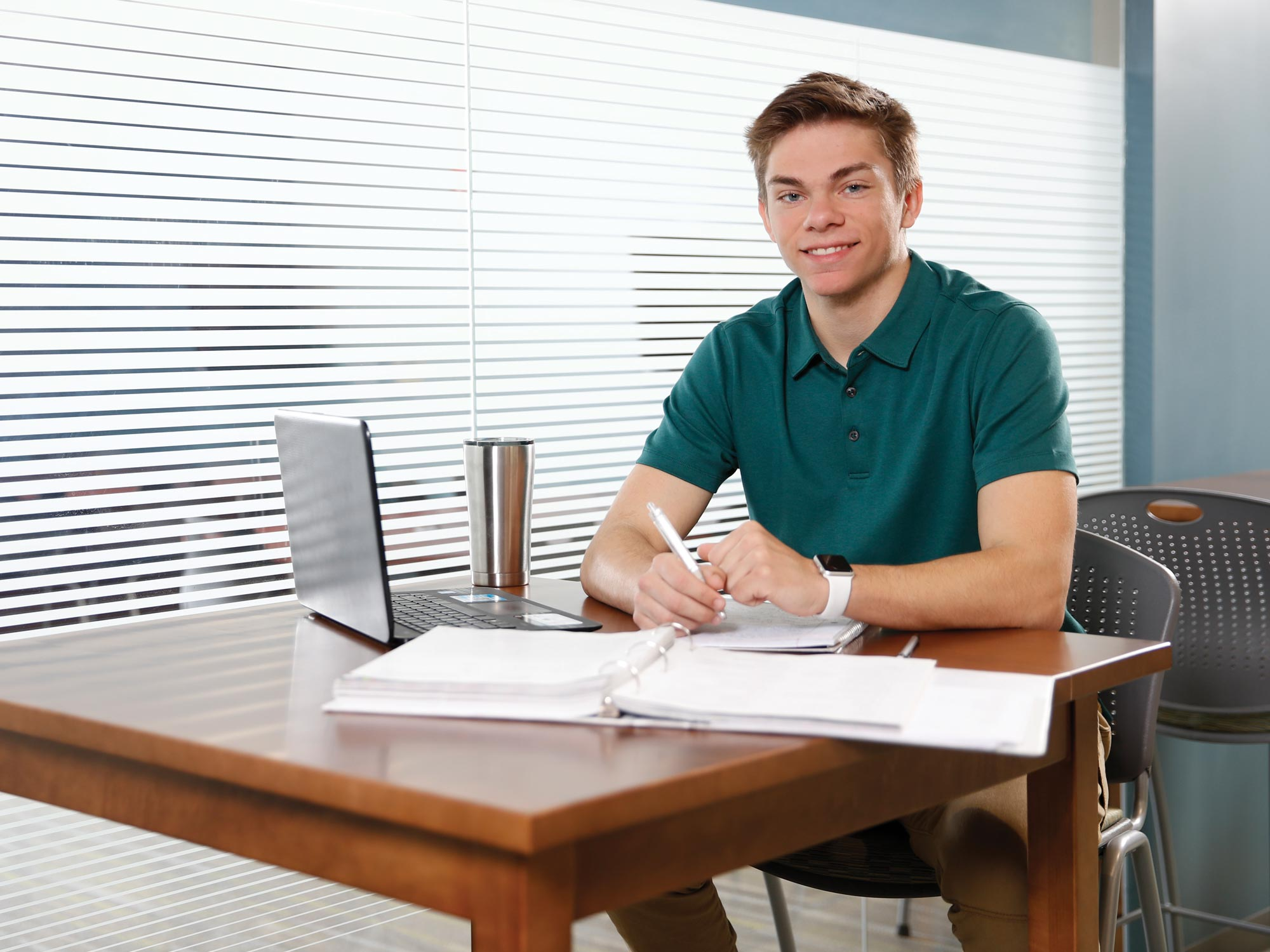 Male student sitting at table with binder and laptop