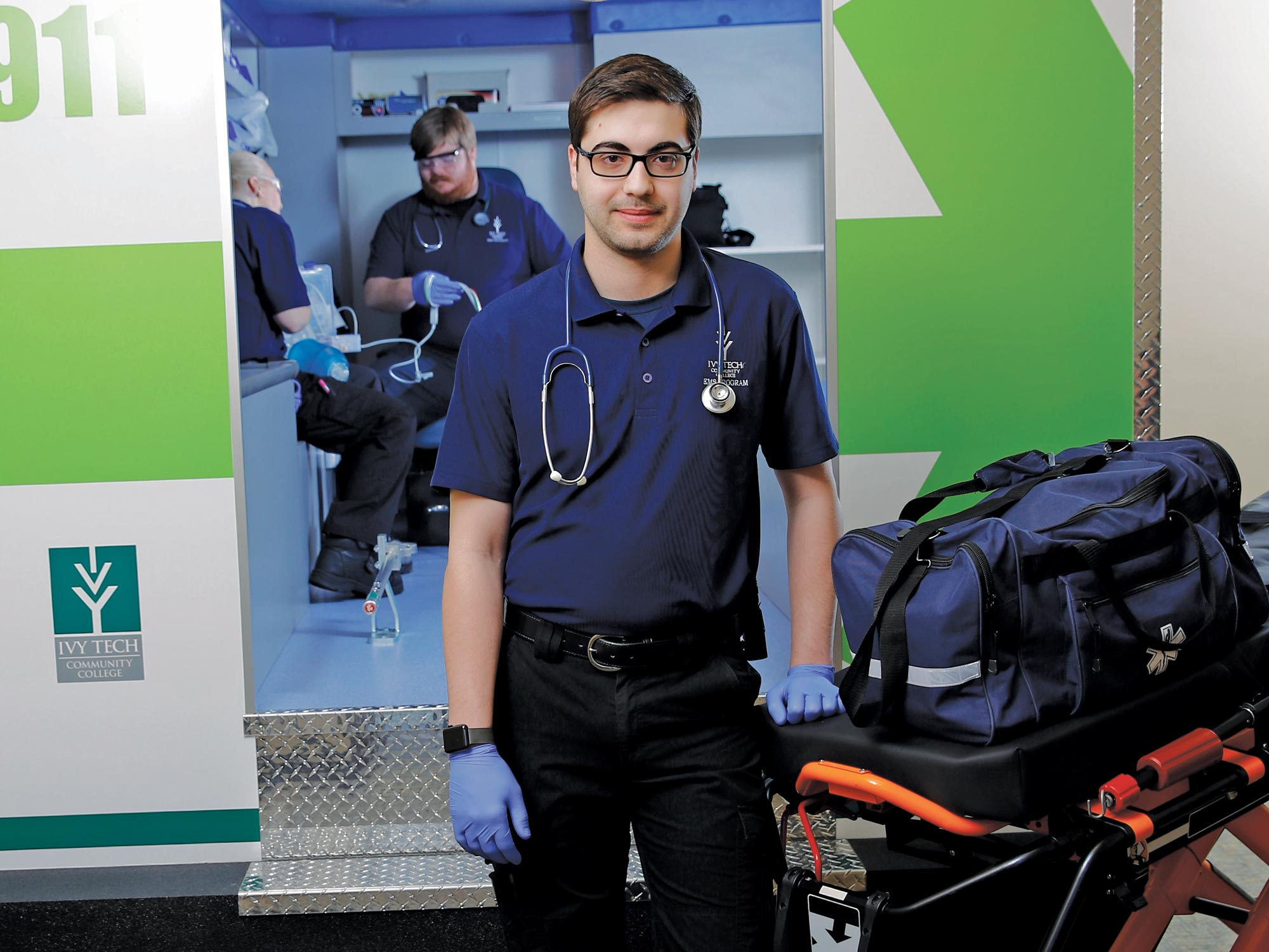 Male medical student standing next to ambulance