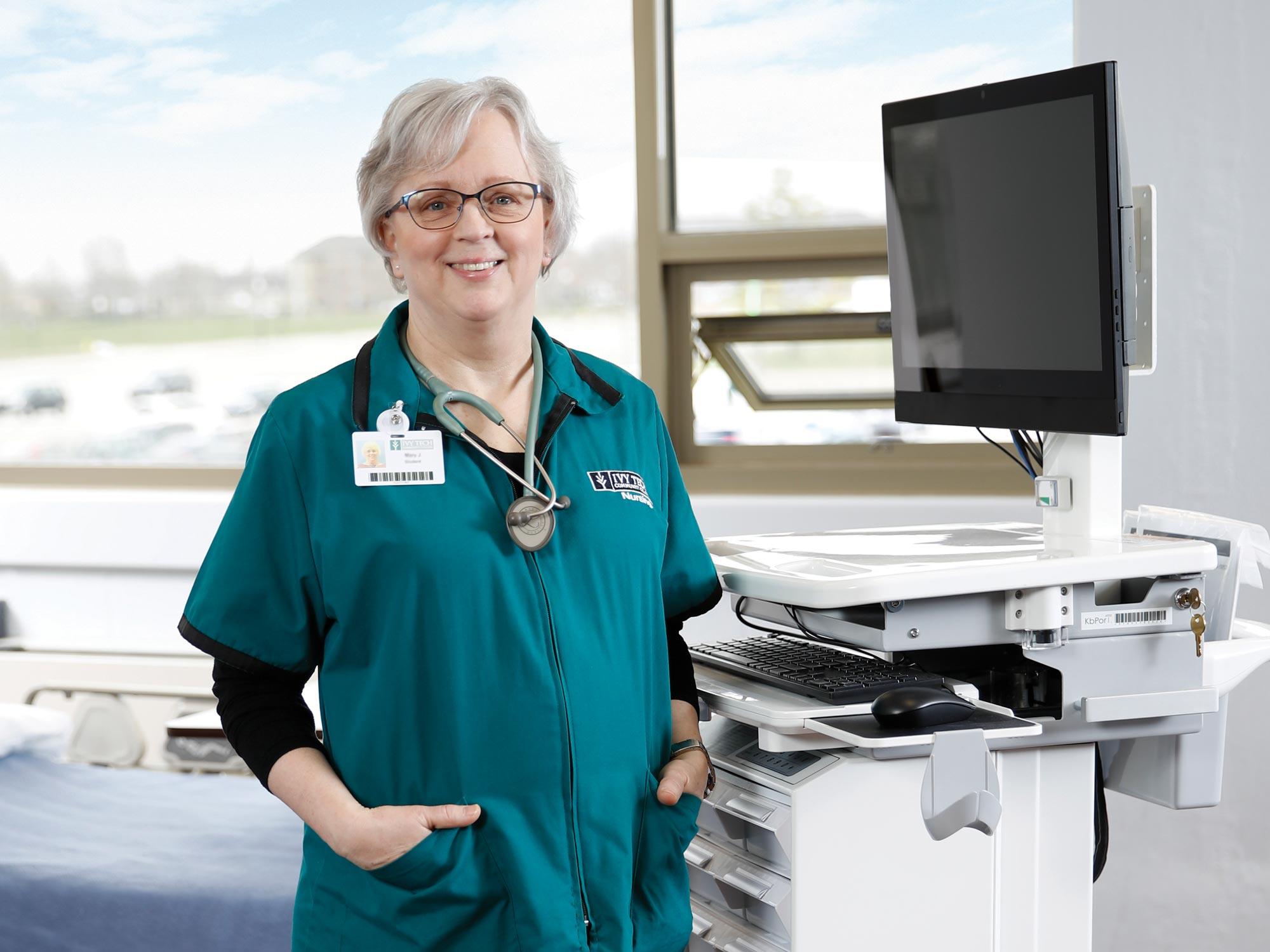 Older female student standing at nurse's station