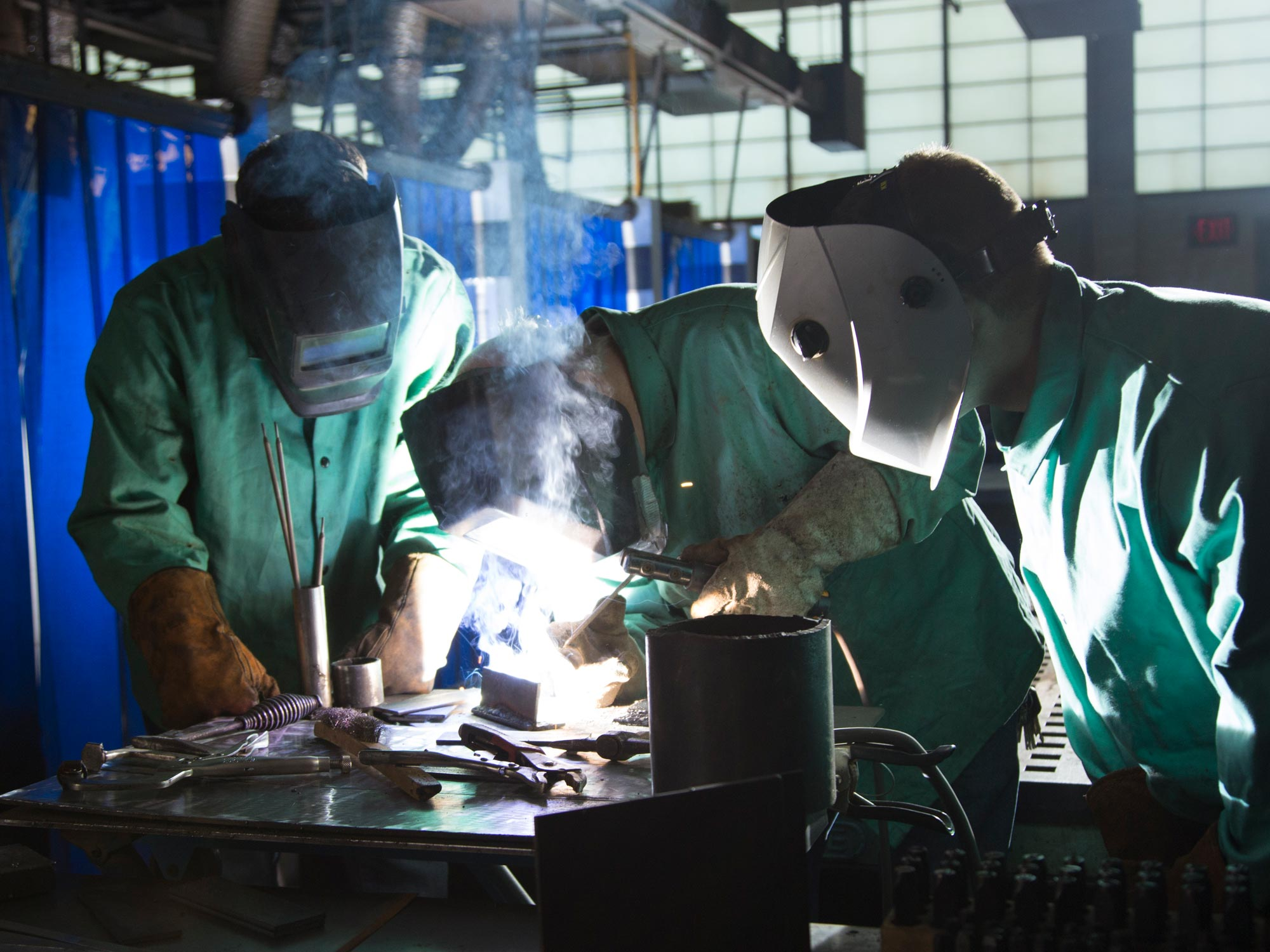 Several students welding with face masks